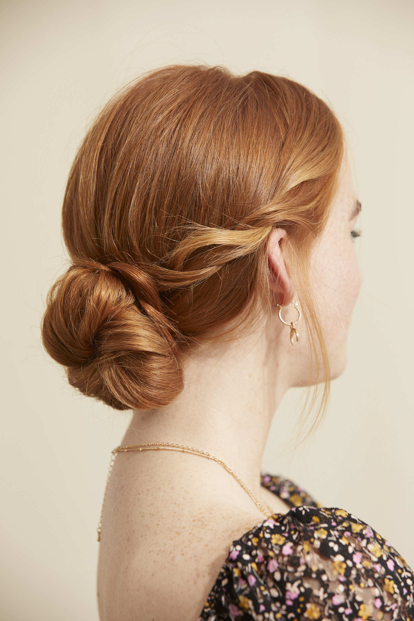 Woman wit ginger hair in lwo chignon updo