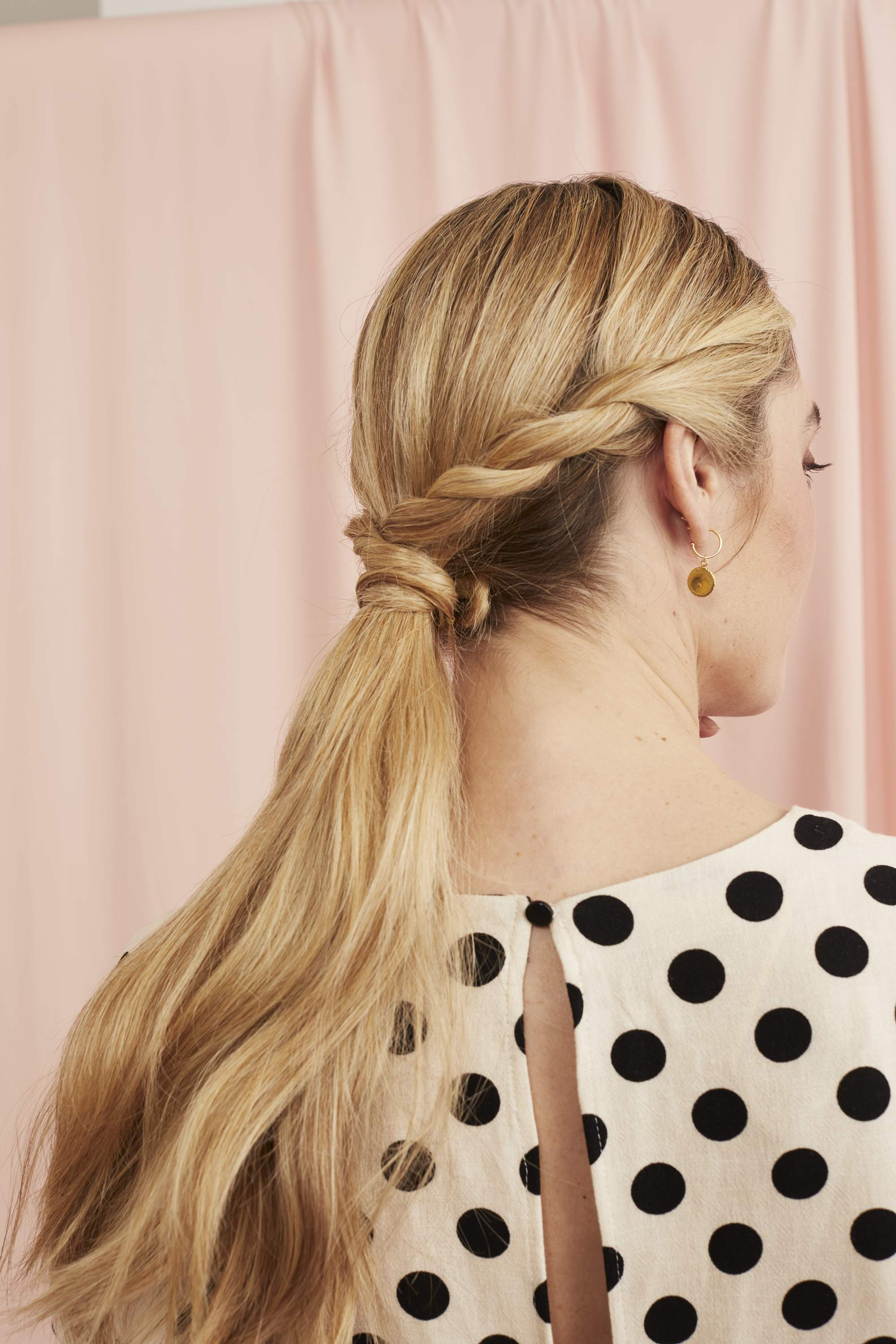 Woman with blonde hair in twisted wrapped ponytail