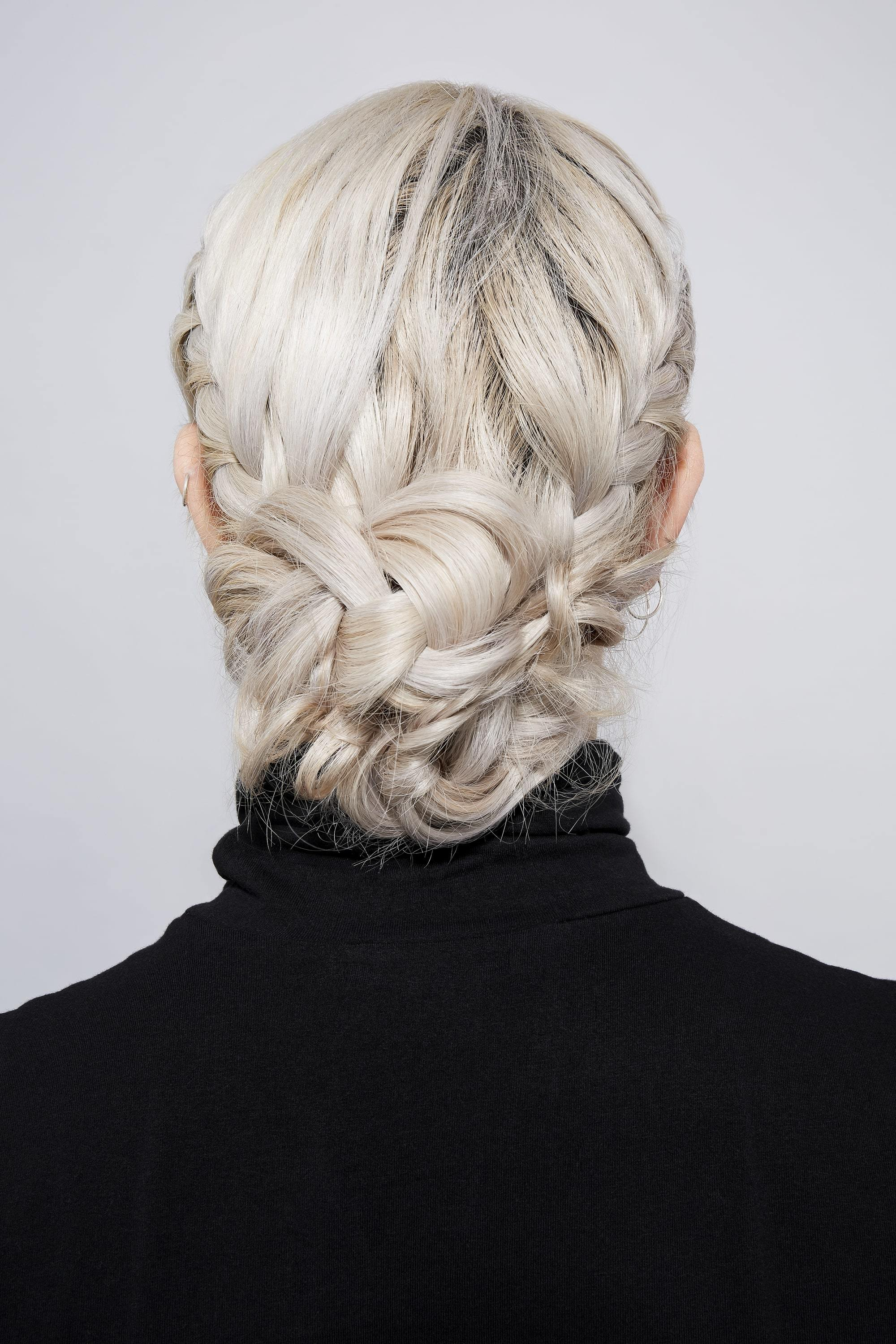 Woman with ice blonde hair in two French braids tied into a bun