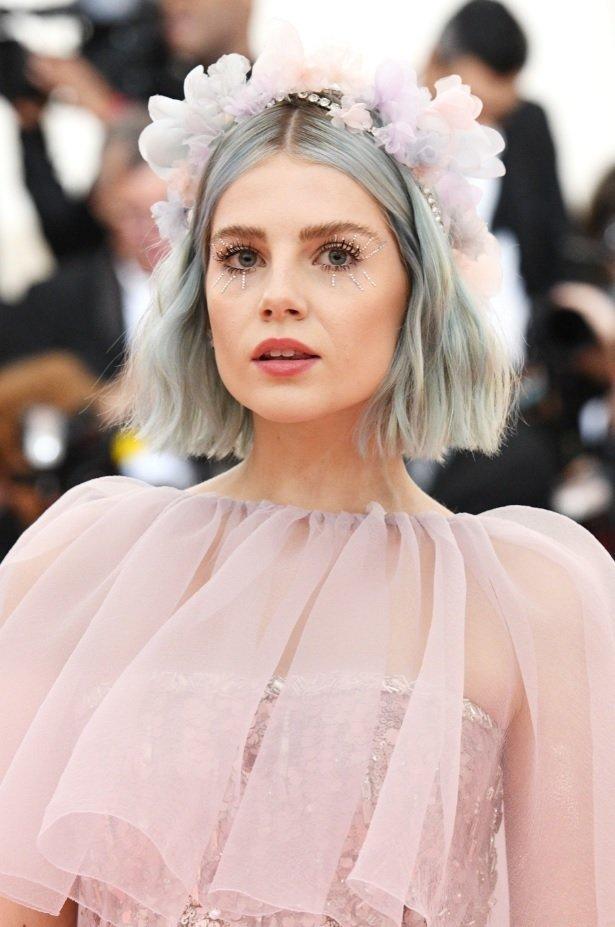 Lucy Boynton with a blue wavy bob with a floral headband