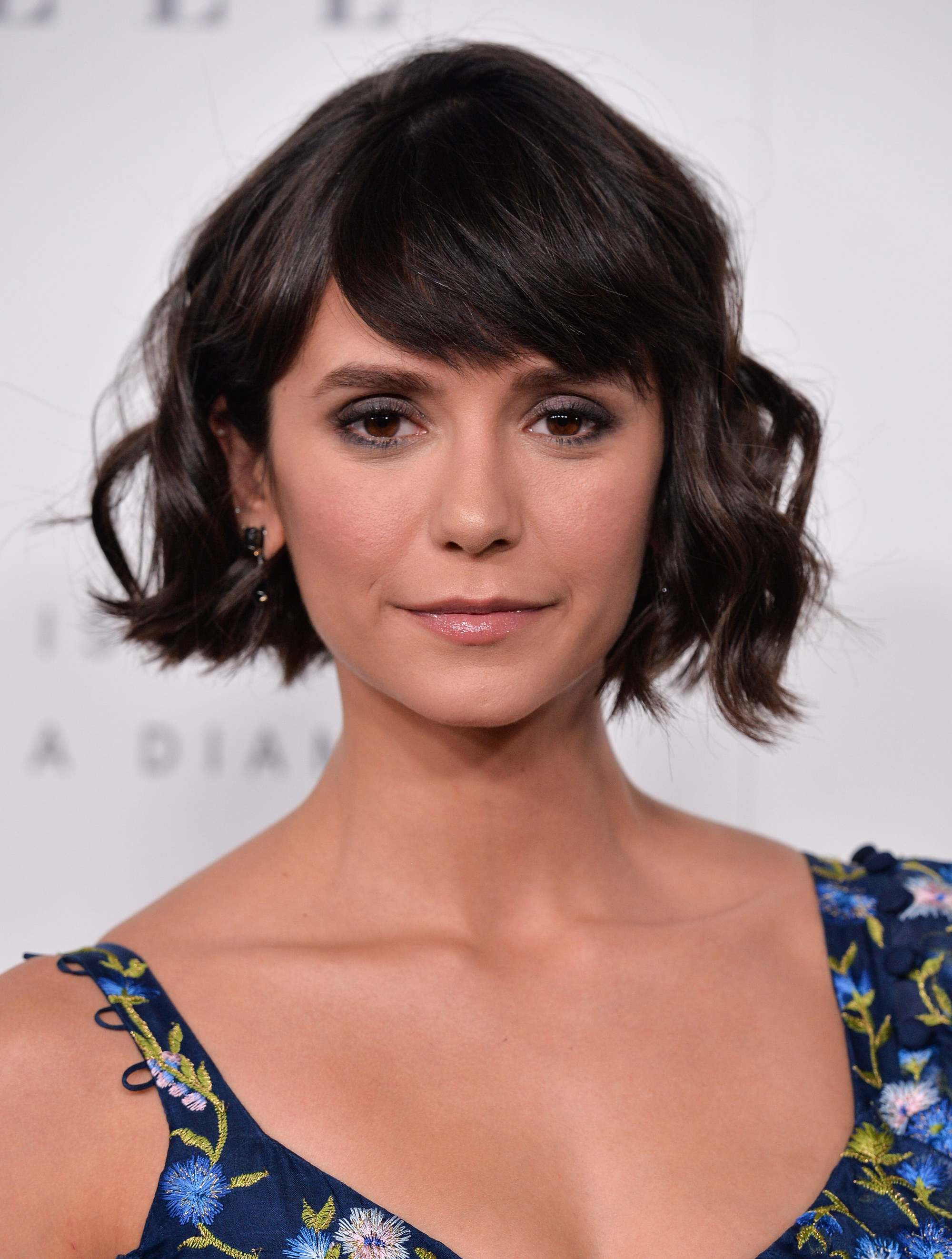 Nina Dobrev with a dark brunette wavy bob with a fringe