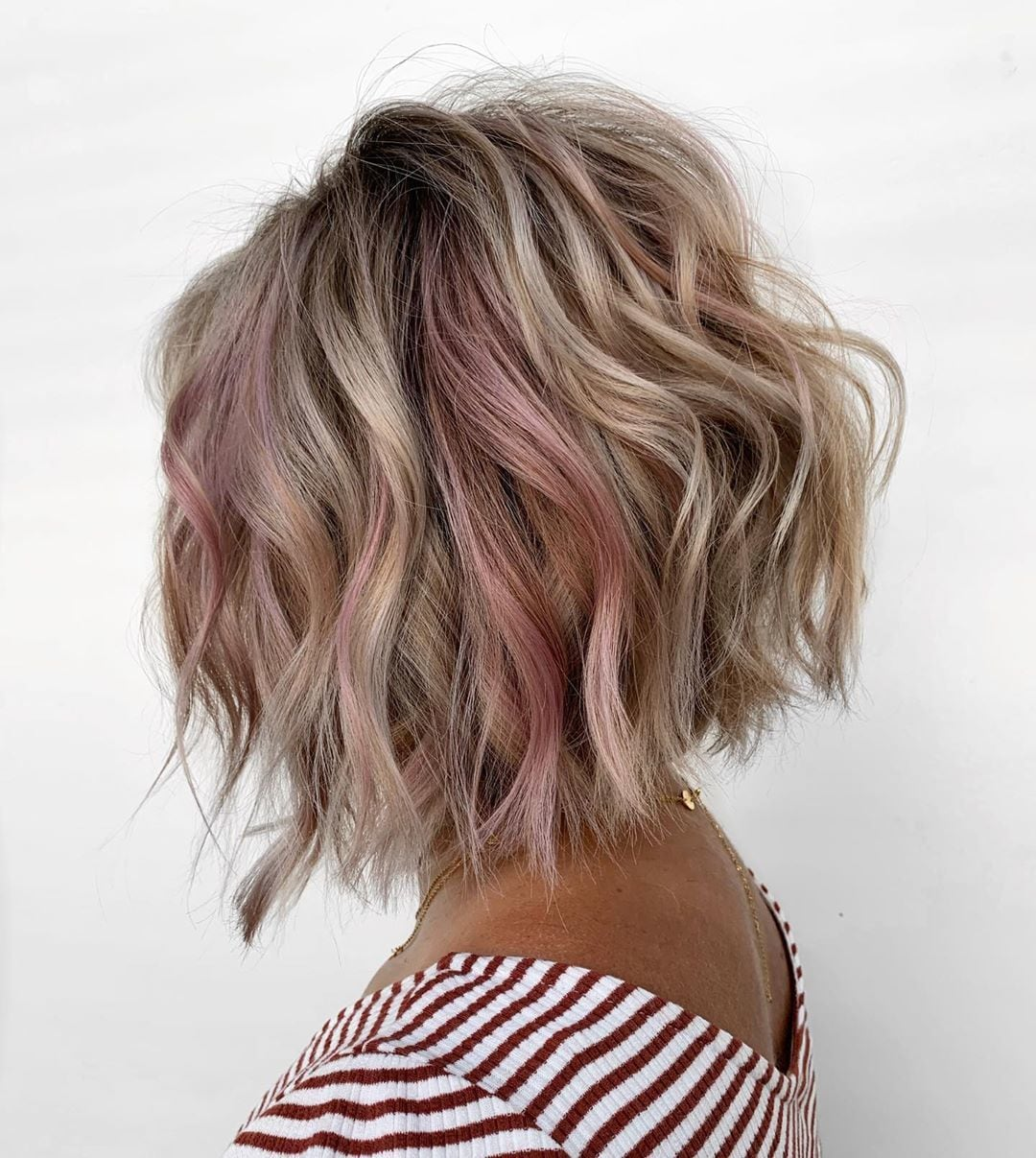 Blonde woman with a wavy stacked bob with pink highlights