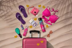 Pink suitcase on the sand with beach products and VO5 spray