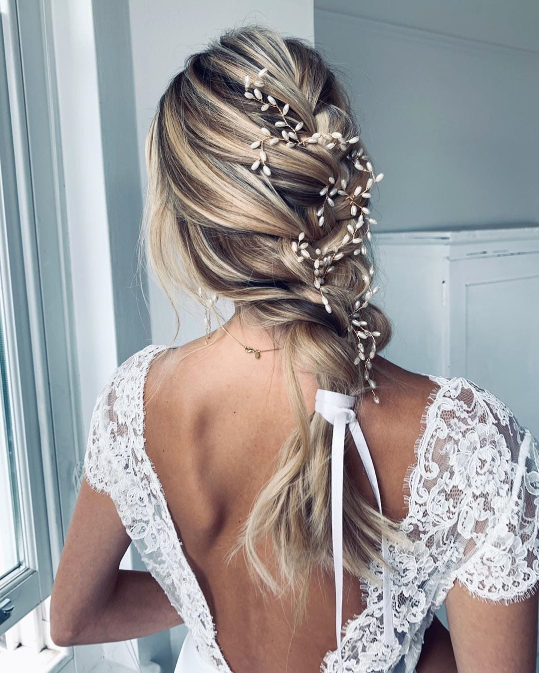 Bride with messy French braid with pearl pins and white hair bow