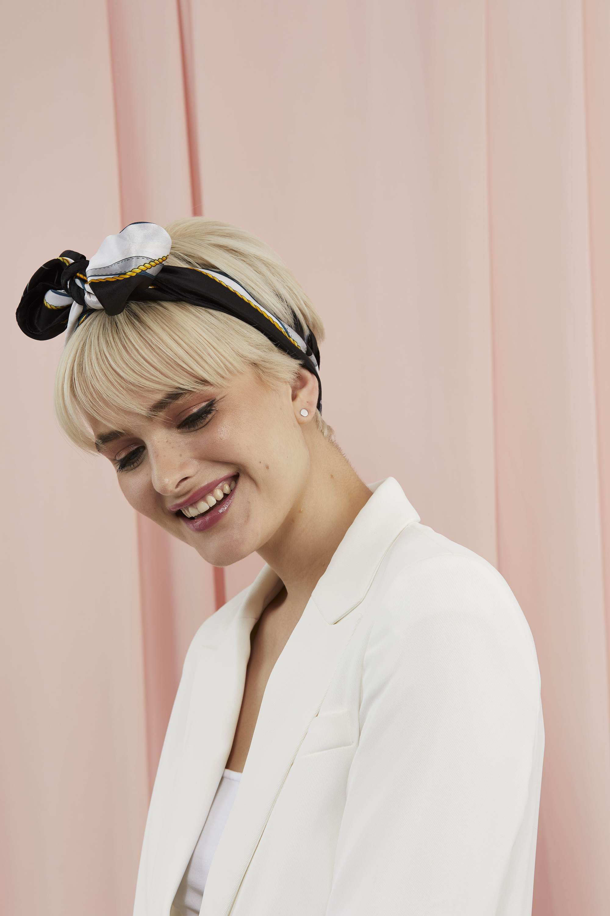 Woman with a platinum blonde pixie cut with a scarf tied around