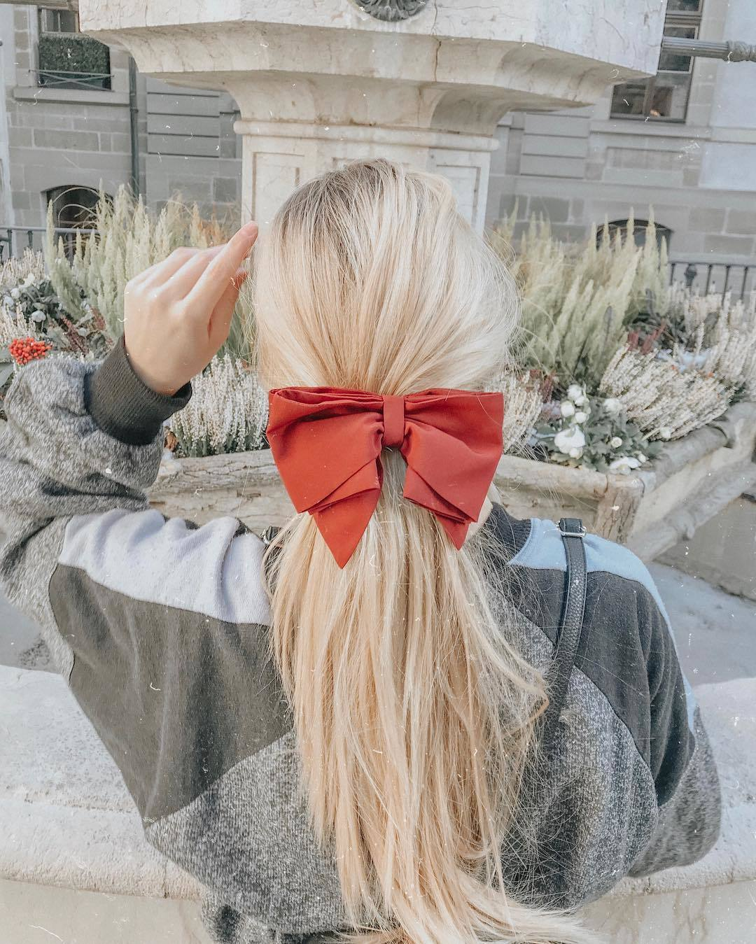 Blonde woman with a ponytail with a red bow