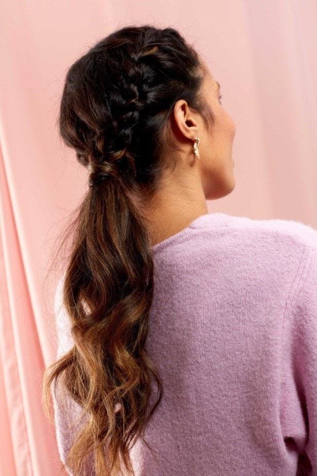 Brunette woman with a braided curly low ponytail