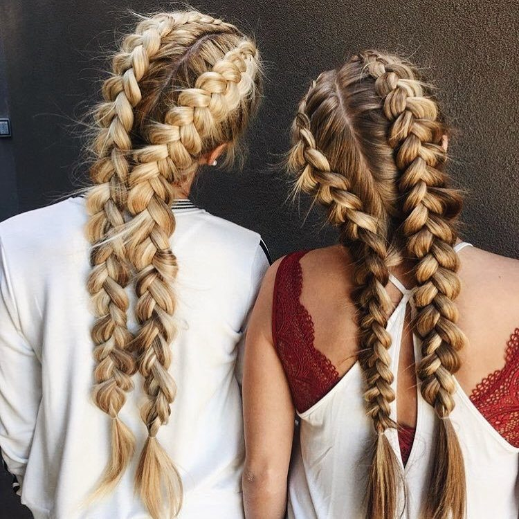 Two girls with long hair styled into braided pigtails
