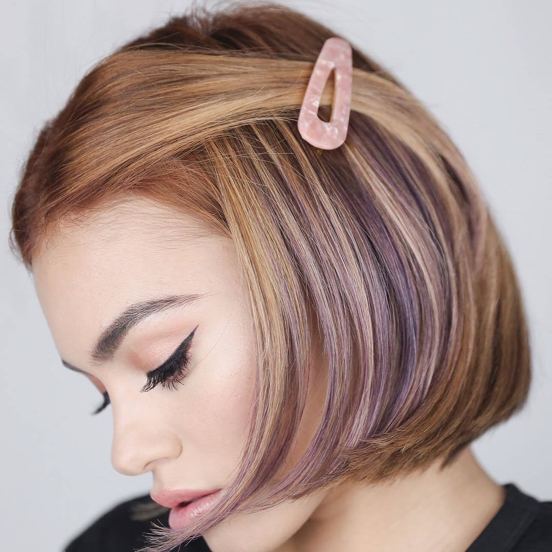 Woman with a purple highlighted bob with a pink snap clip