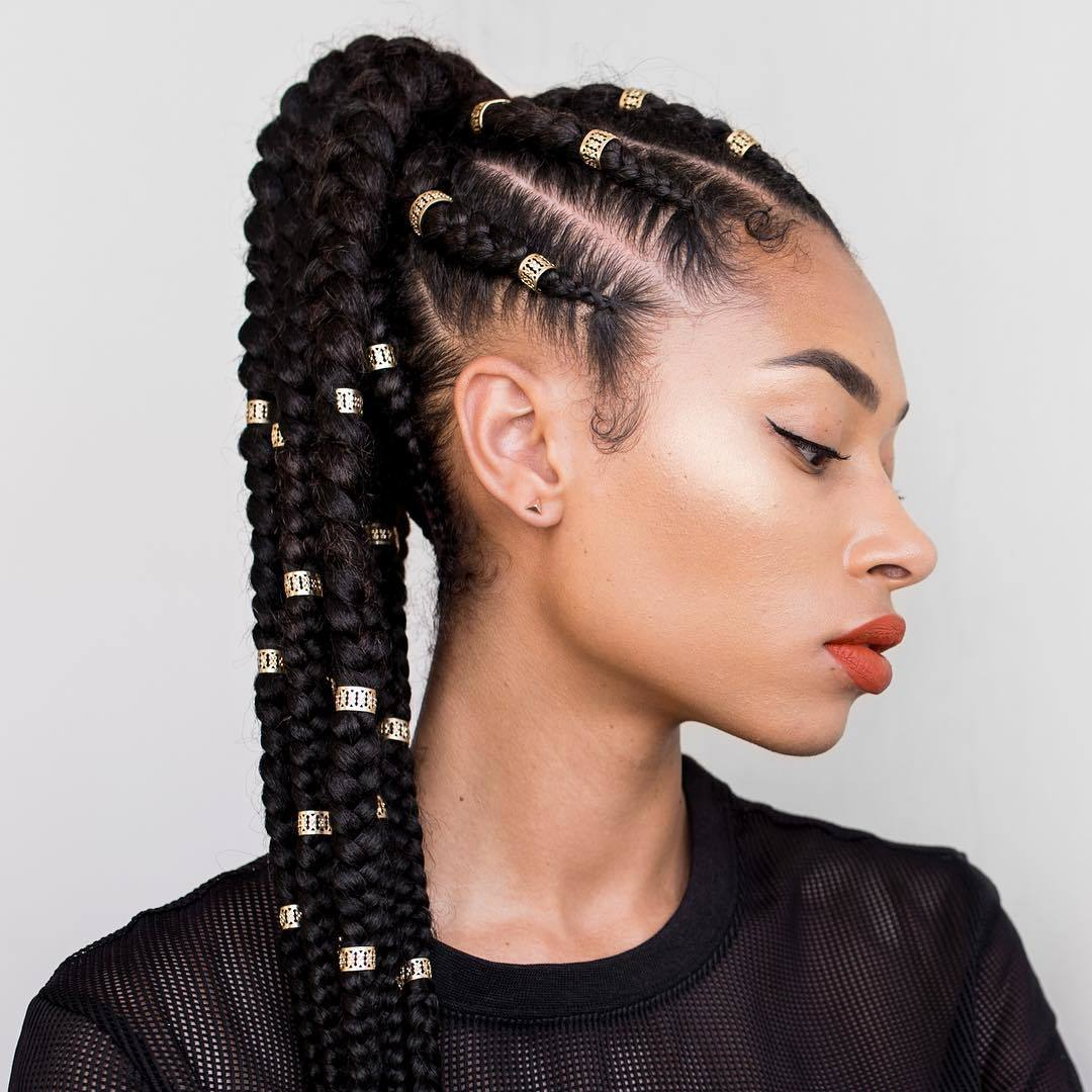 Woman with a cornrow ponytail with gold cuffs