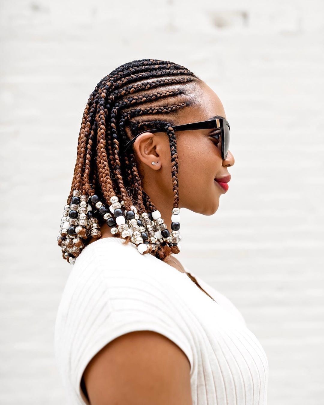 Woman with shoulder length cornrow hairstyle with beads