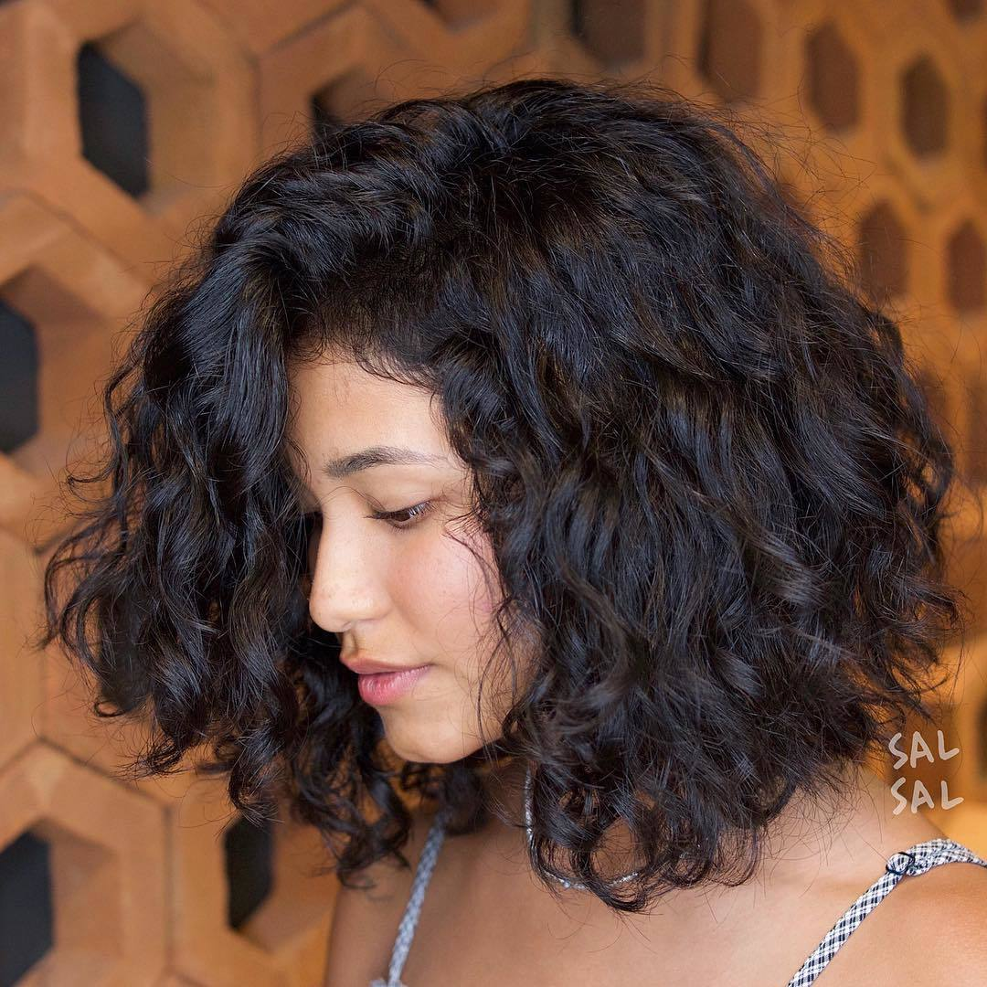 woman with natural curly brown hair cut into an asymmetrical lob
