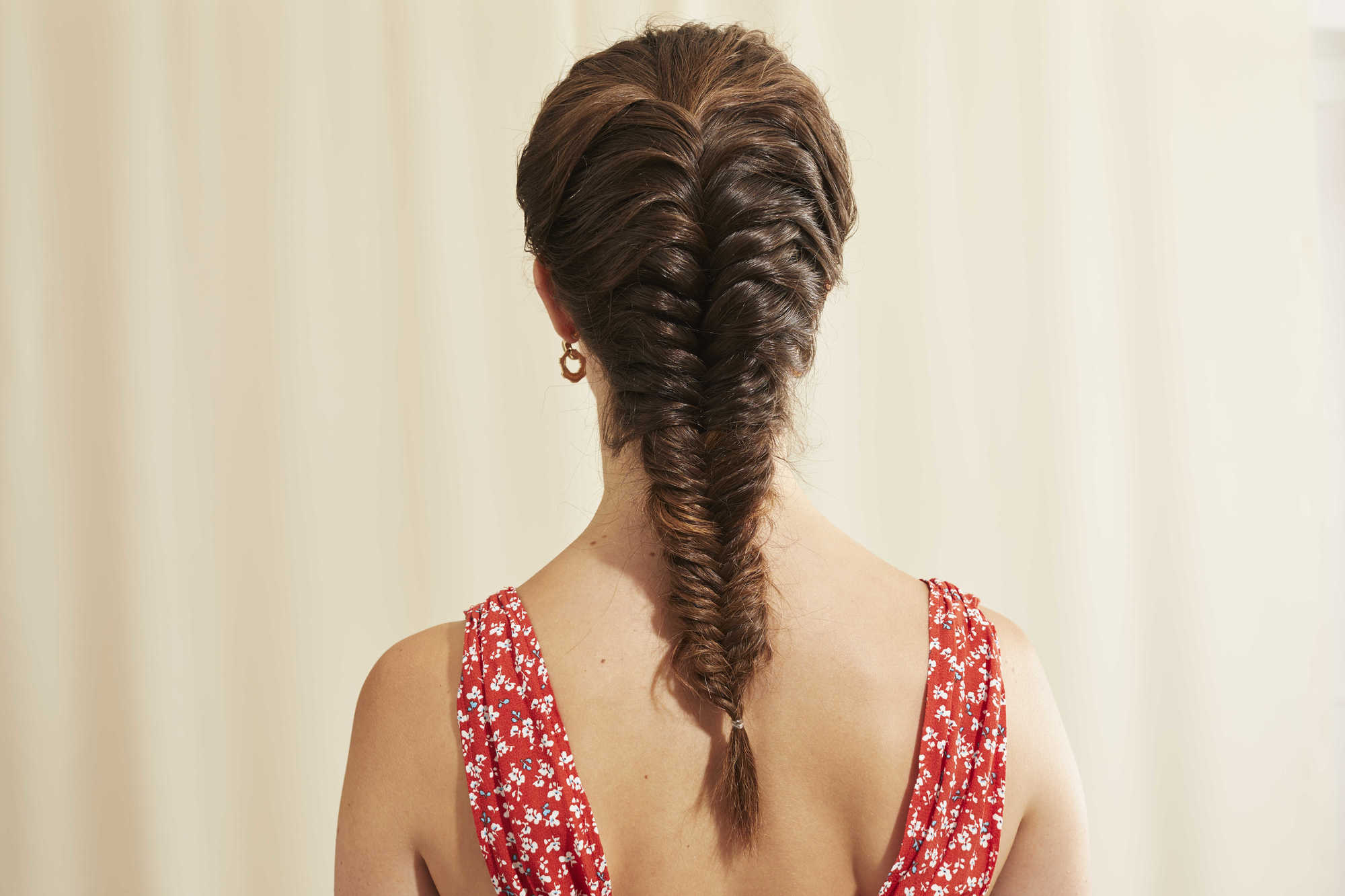 Woman with long brown hair styled into a fishtail braid