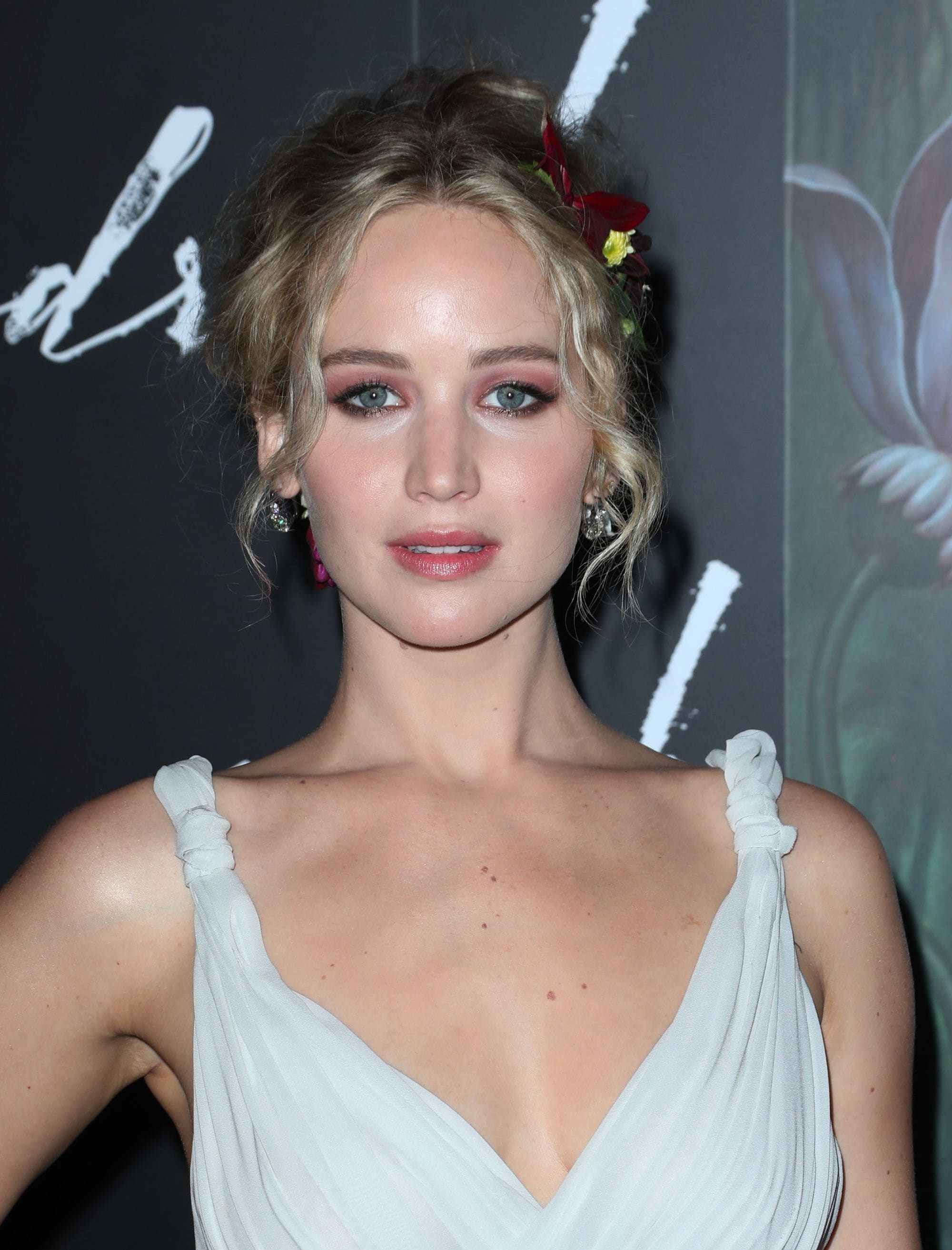 Jennifer Lawrence with dirty blonde hair styled into a messy updo with flowers