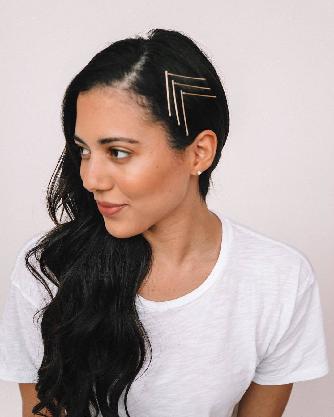 Woman with long dark brown wavy hair with bobby pins
