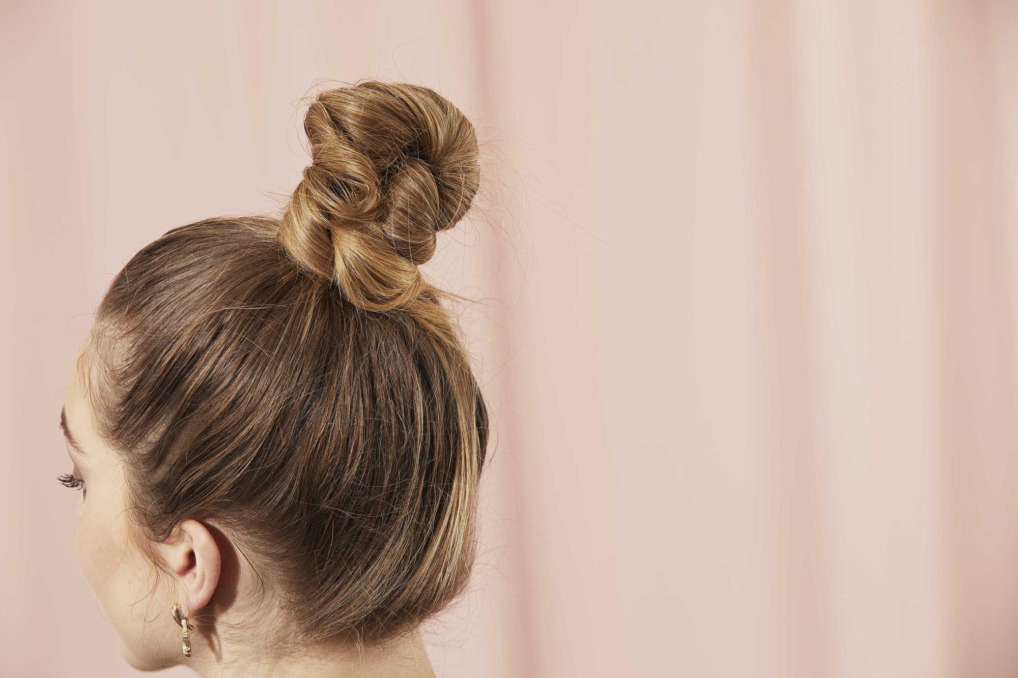 Woman with dark blonde hair styled into a top knot