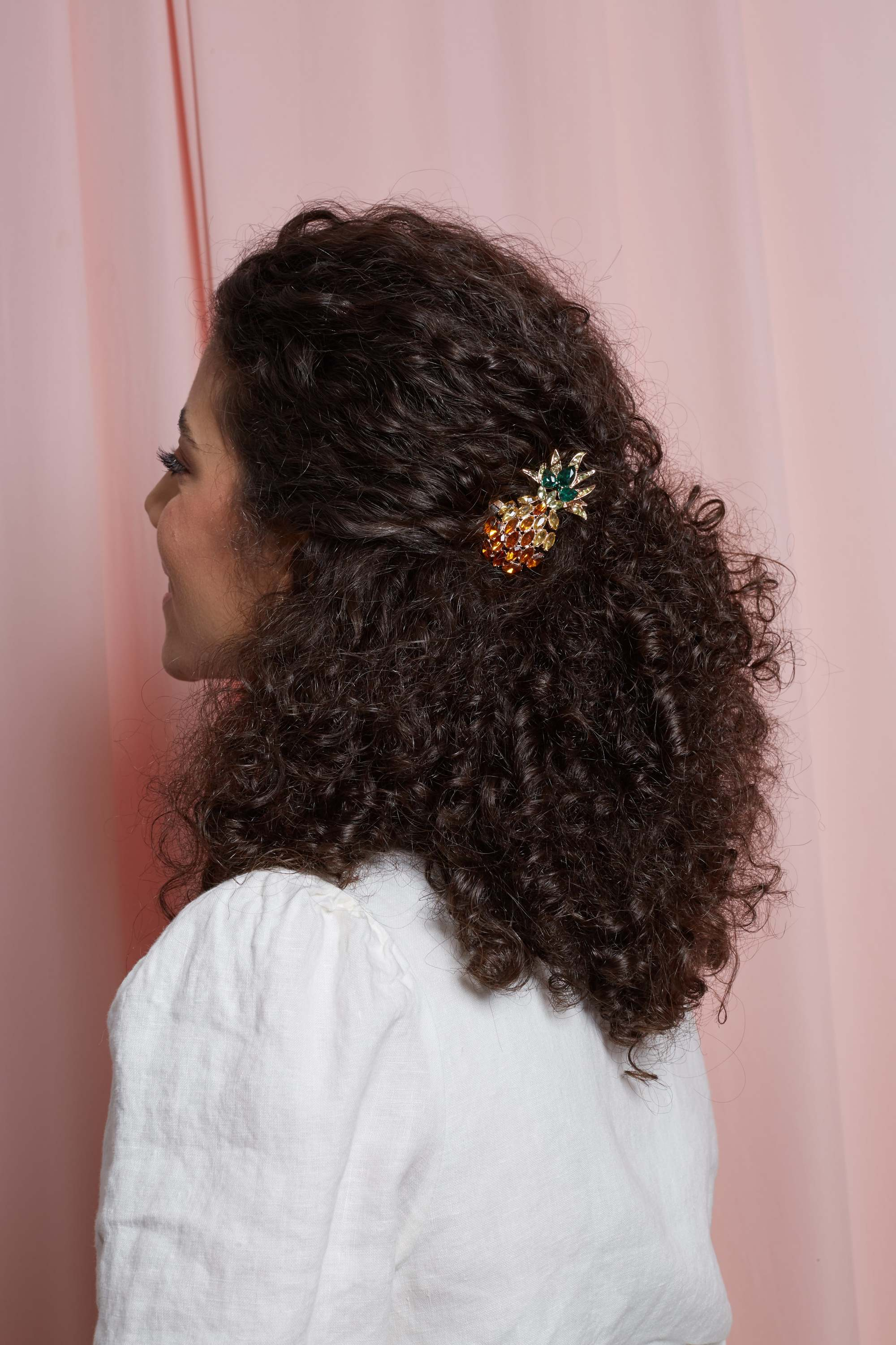 Brunette with naturally curly hair in a half-updo with a pineapple clip