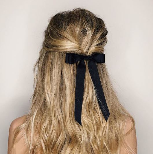 Woman with long blonde hair in half-up with ribbon bow