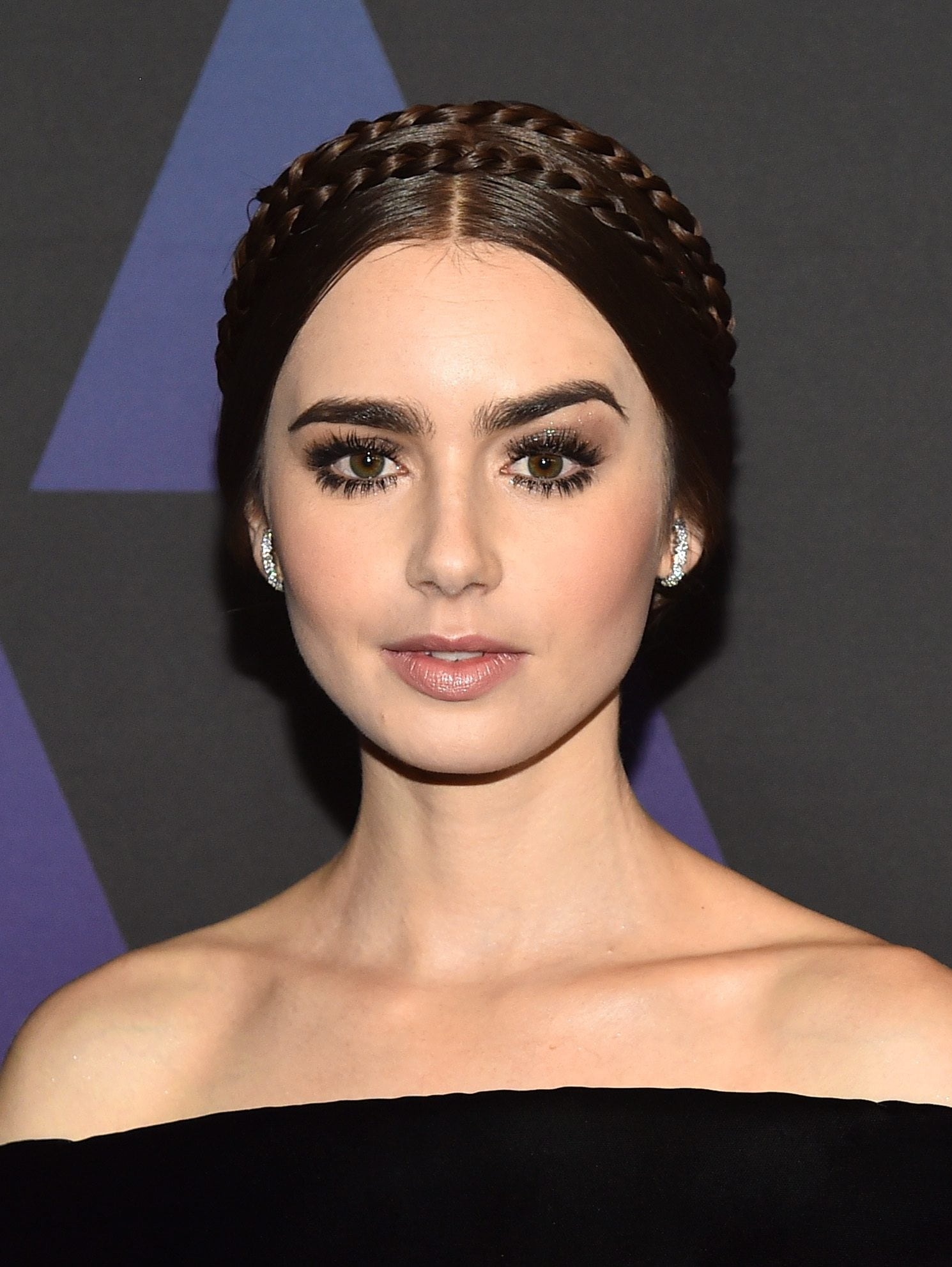 Lily Collins with her dark hair styled into a double halo braid hairstyle