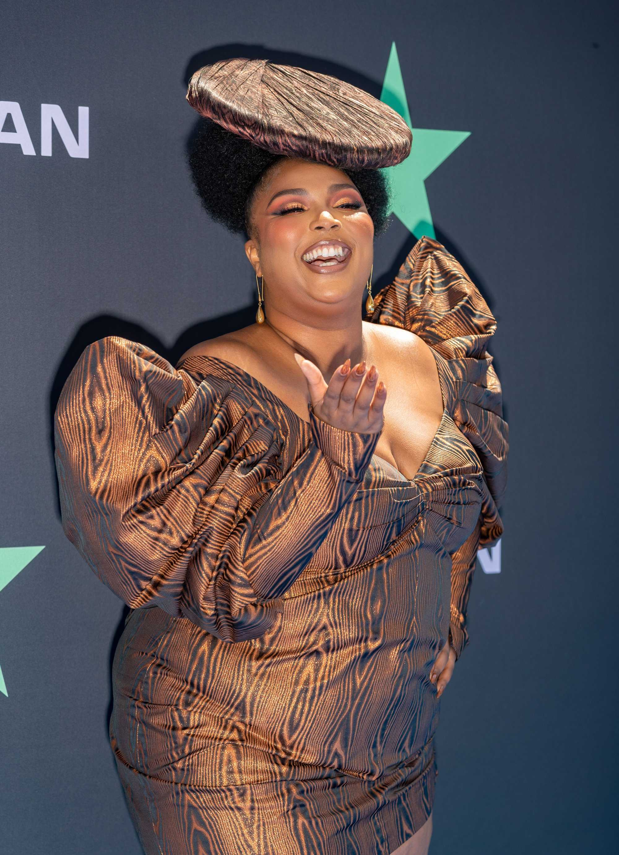 Lizzo with her natural hair in an updo with a wood effect fascinator