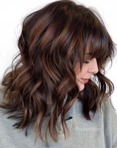 Woman with wavy brown balayage hair with bangs