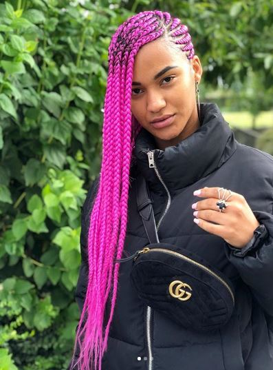 Woman with long pink cornrows to the side