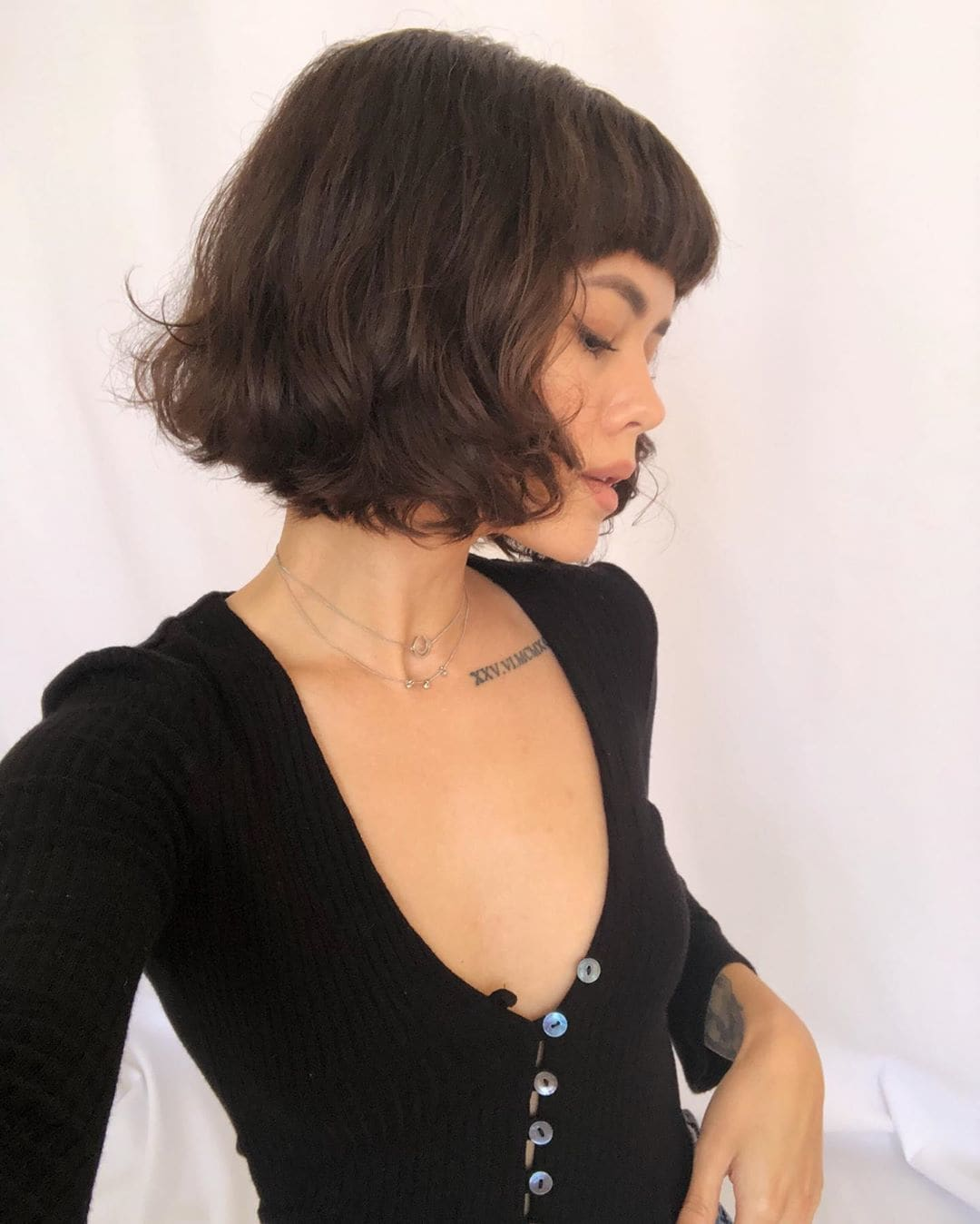 Woman with loose wavy bob with full bangs