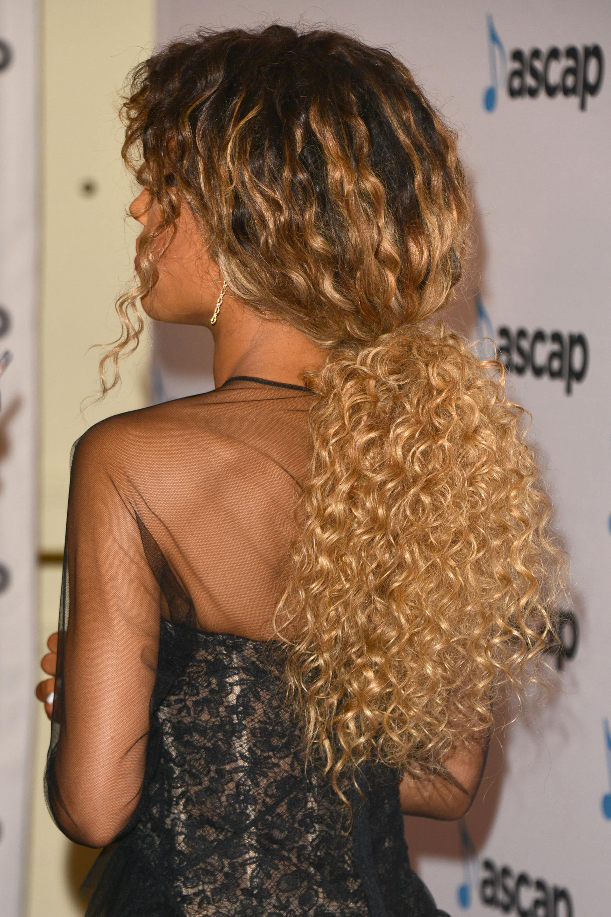 Woman with long dark roots and golden blonde curls styled into a low ponytail