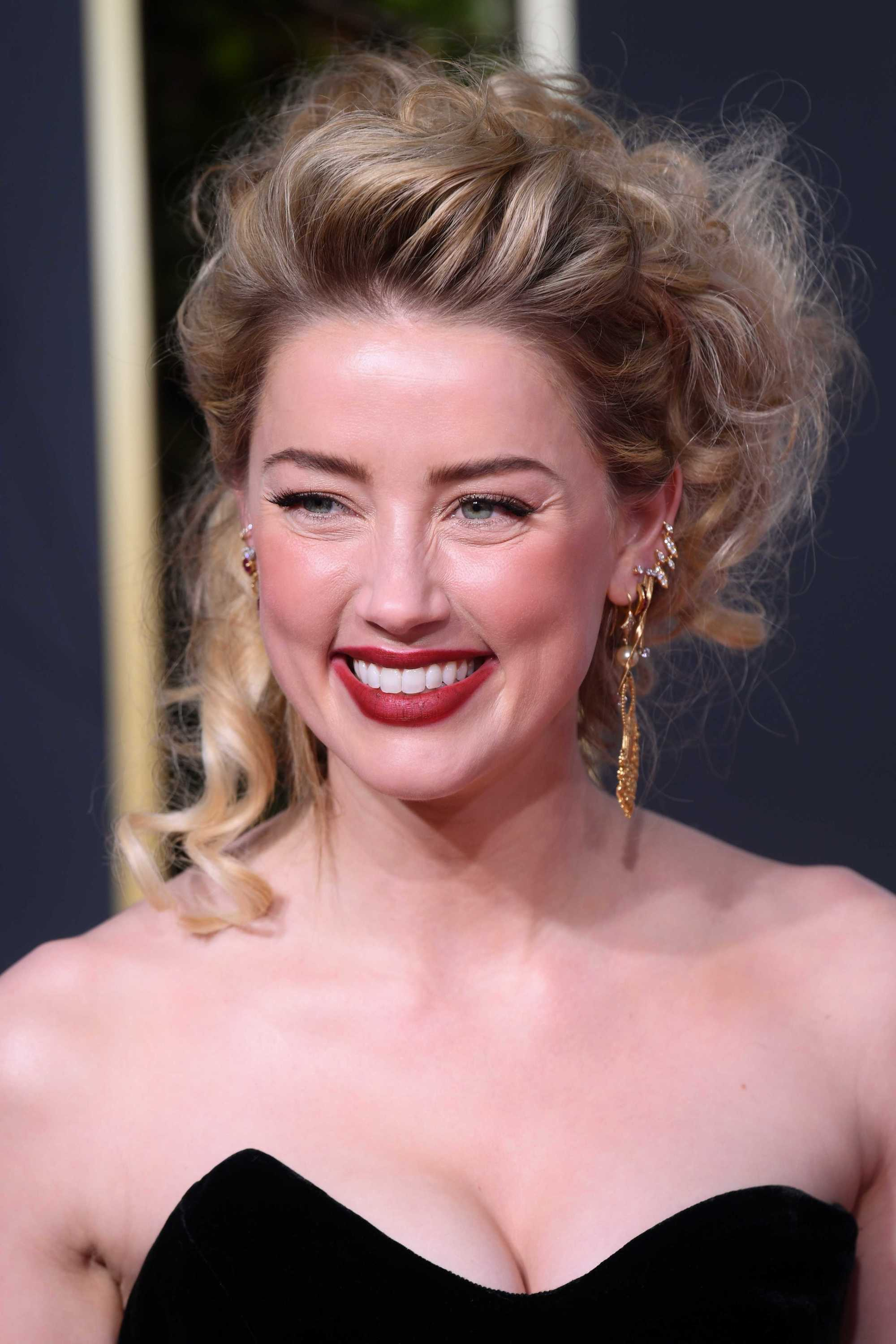 Amber Heard with her ash blonde hair styled into swept back curly updo