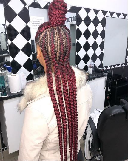 Woman with red cornrows in half-up bun