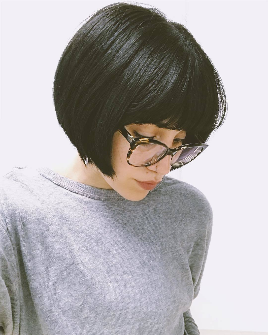 Woman with super short rounded dark brown bob with thick bangs