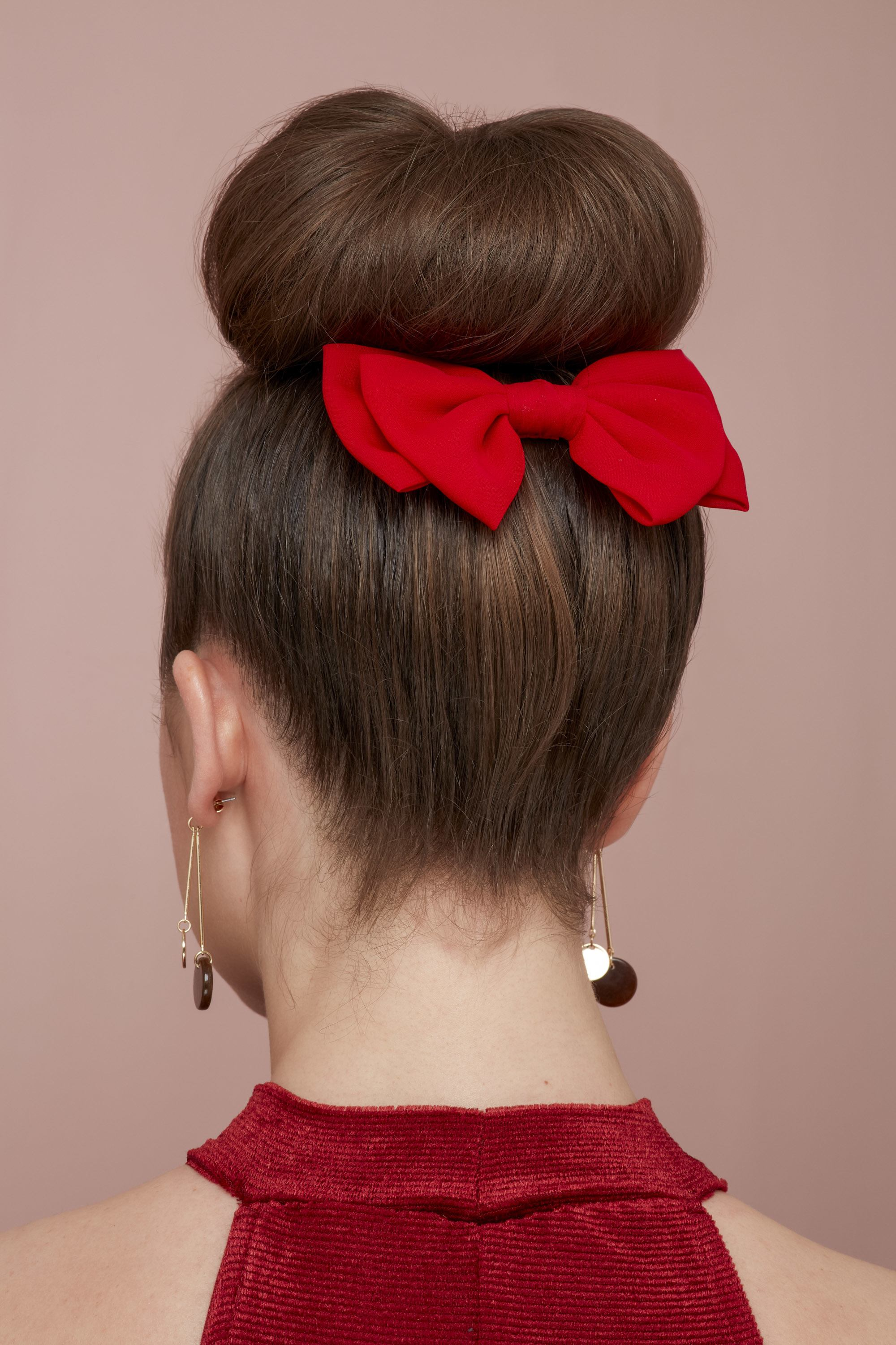Woman with dark hair styled into a bun with red hair bow