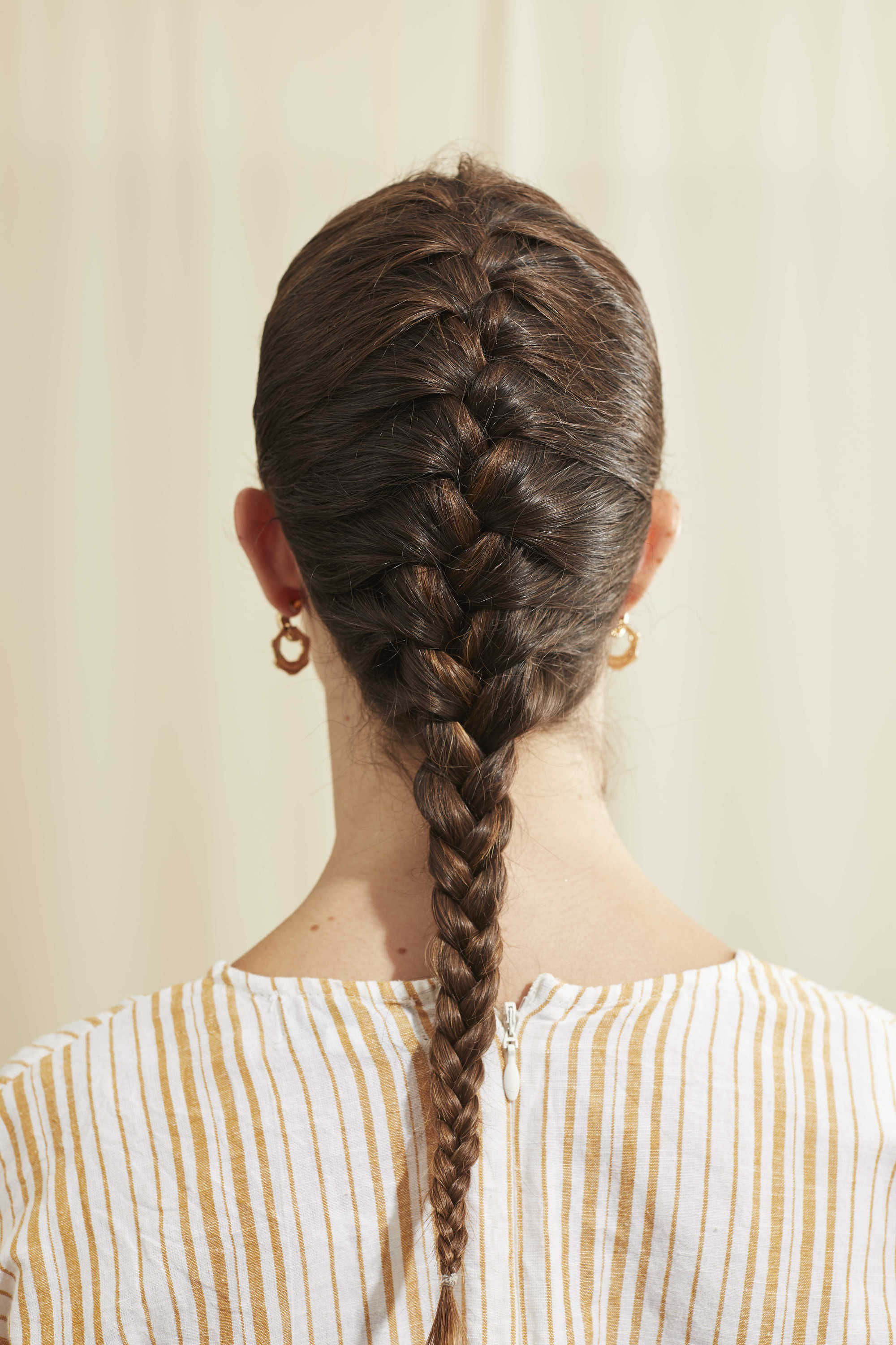 Woman with dark brown hair styled into a French braid