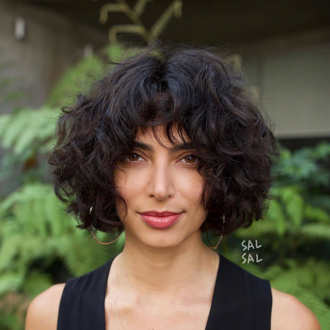 Woman with short curly brown bob with curly bangs