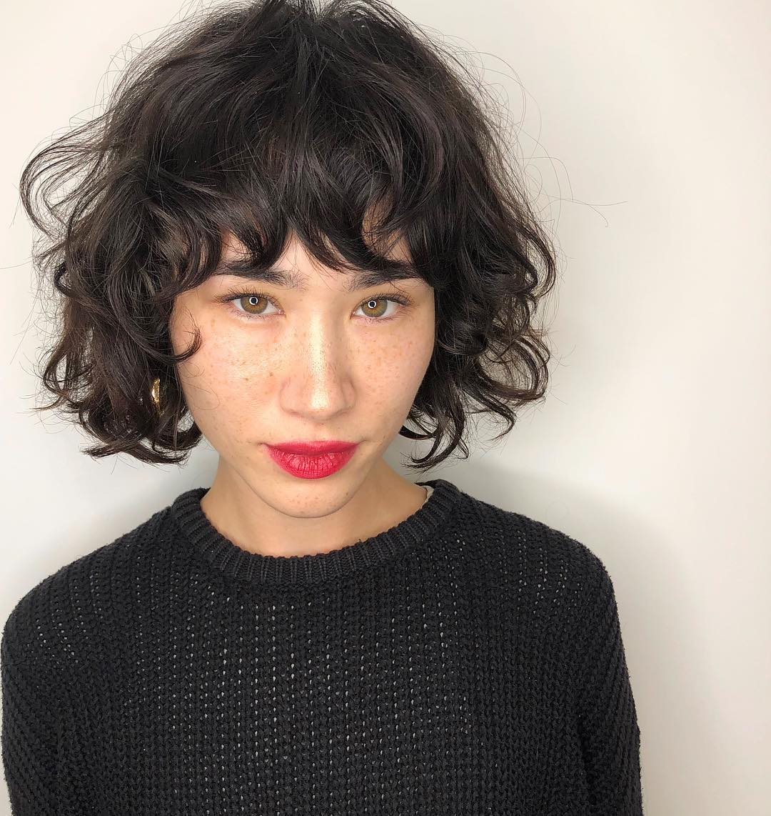 Woman with dark, short messy bob with messy bangs