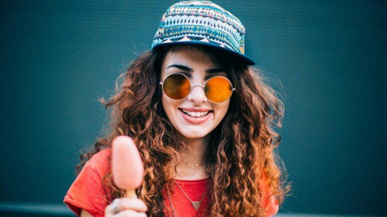 Woman with spiral perm wearing a hat, sunglasses and eating an ice lolly