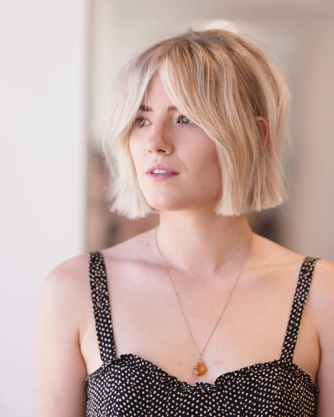 Woman with natural blonde short bob with split bangs