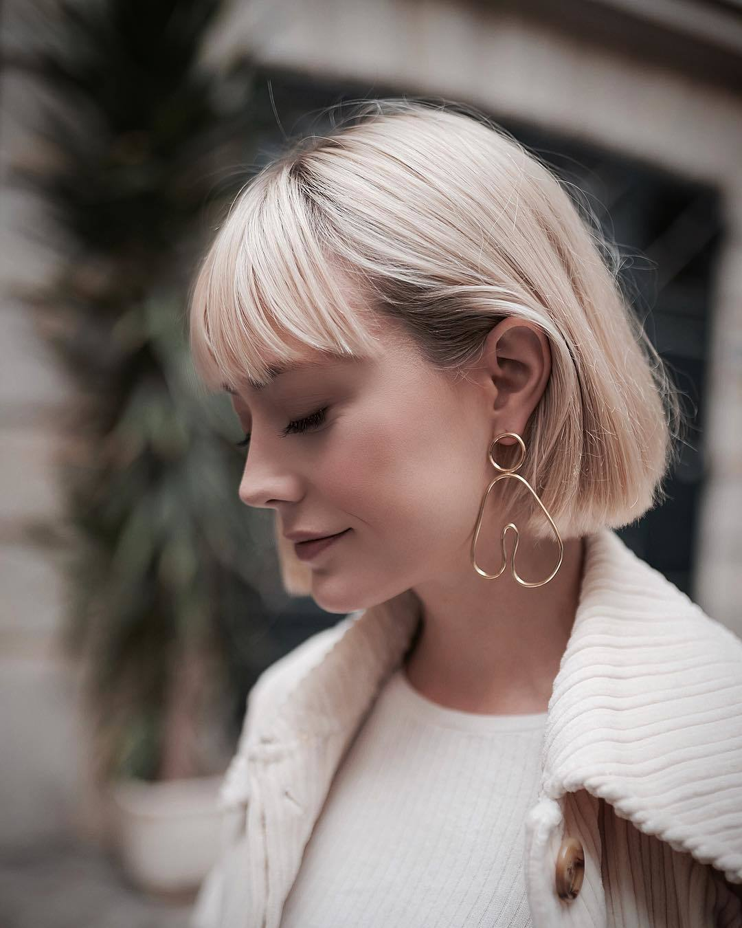 Woman with straight short blonde bob with feathery bangs
