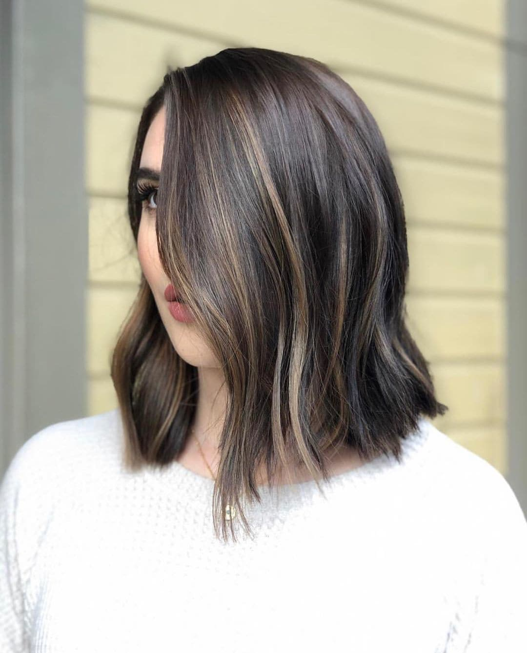 Woman with naturally straight dark hair styled into a subtle textured bob