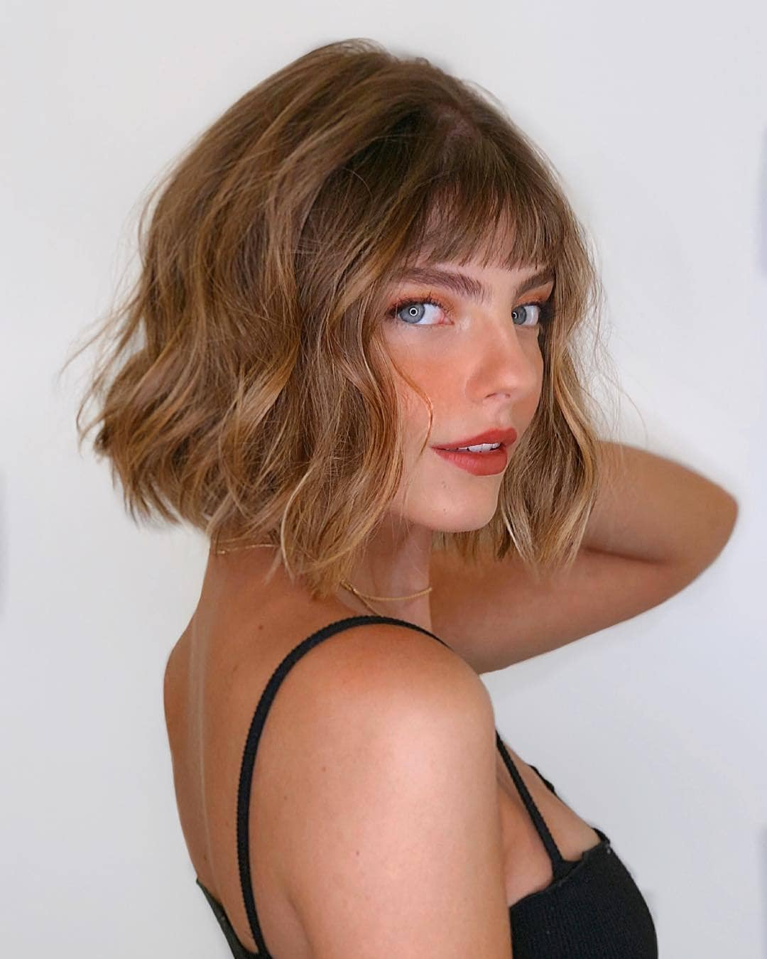 Woman with honey brown short bob with waves and wispy bangs
