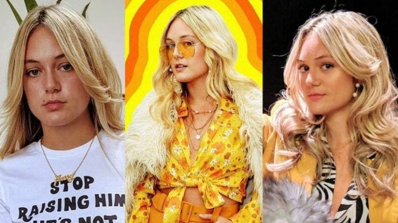 Florence Given with natural blonde long hair styled into bouncy '70s curls