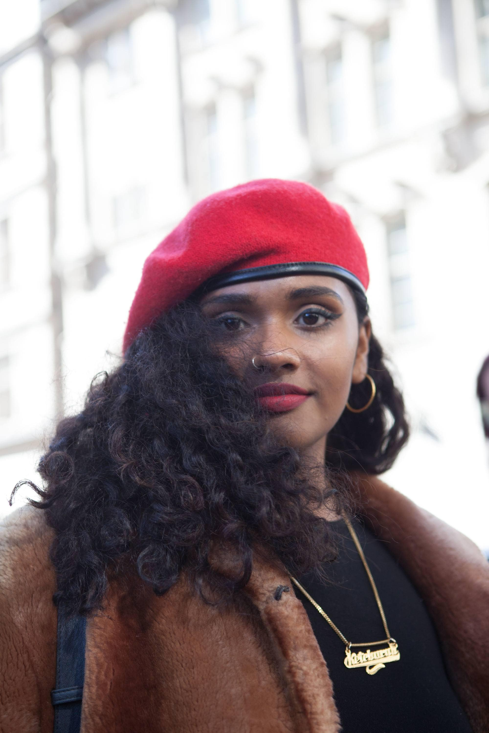 Woman with red beret with fluffy dark long curls at London Fashion Week 2019
