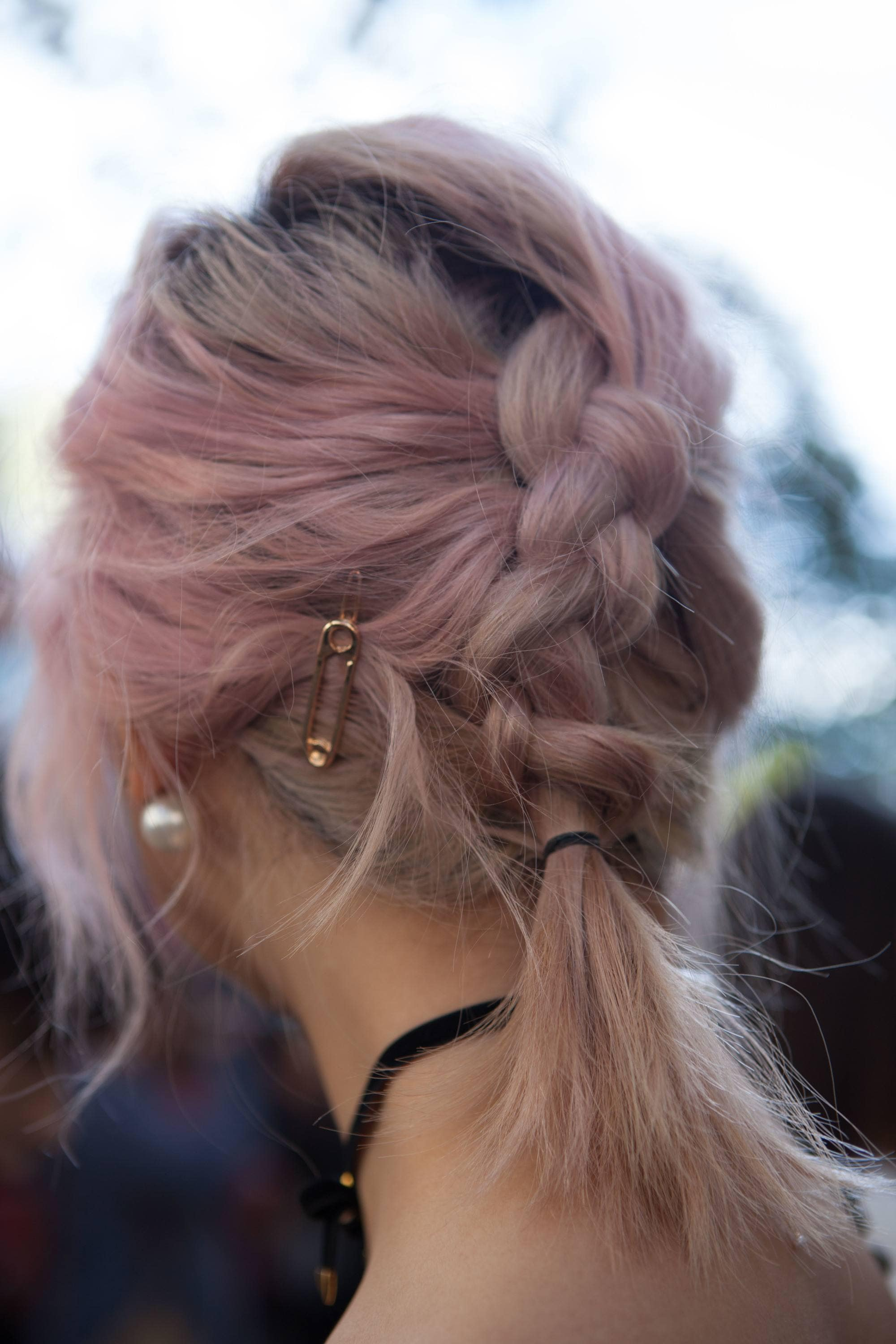 Woman with dark pink short hair styled into Dutch braid