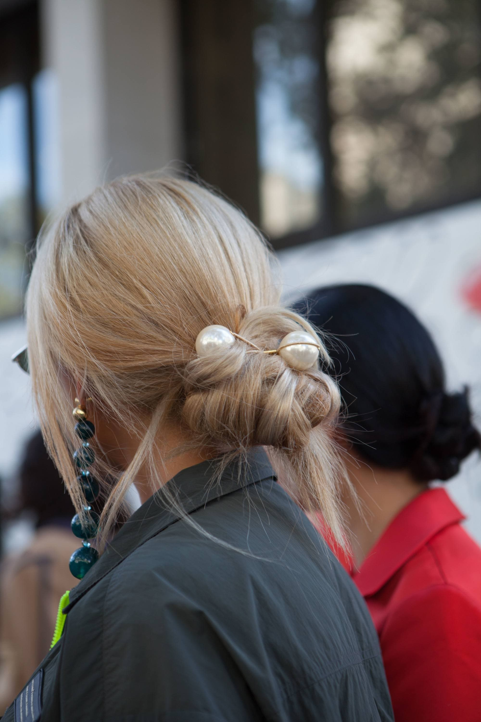 Woman with ash blonde hair styled into a low bun with pearl hair bobbles at London Fashion Week 2019