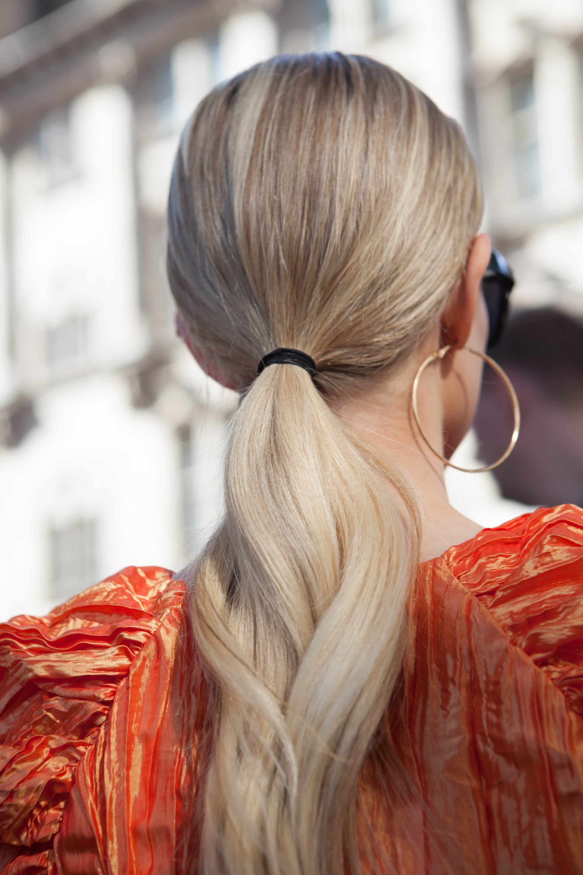 Woman with natural, long and low blonde wavy ponytail