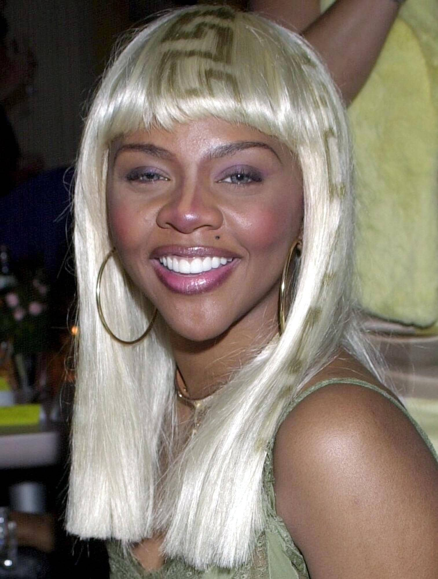 Lil Kim with a blonde wig with bangs and Versace print