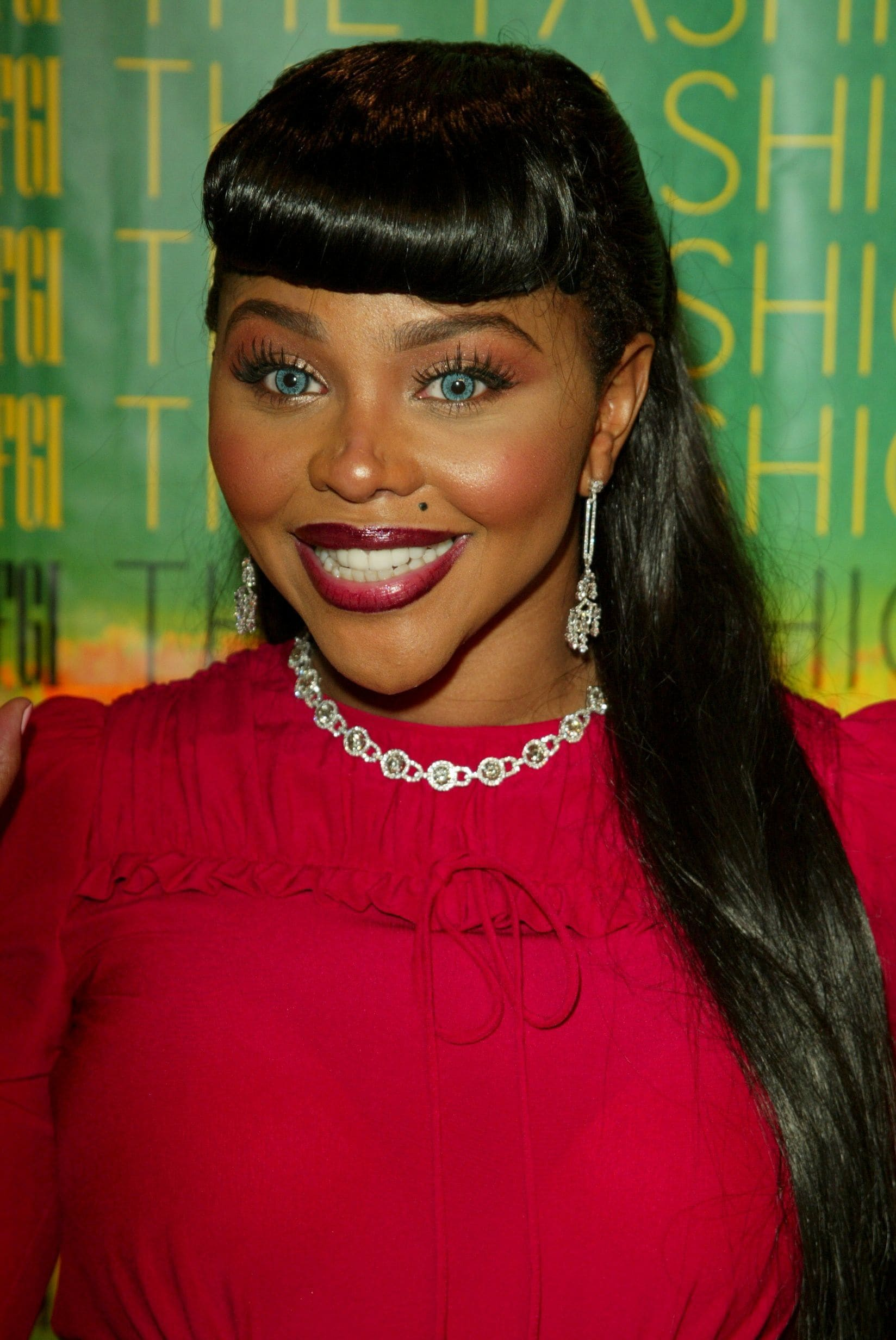 Lil Kim with dark brown hair styled with retro rolled bangs and ponytail