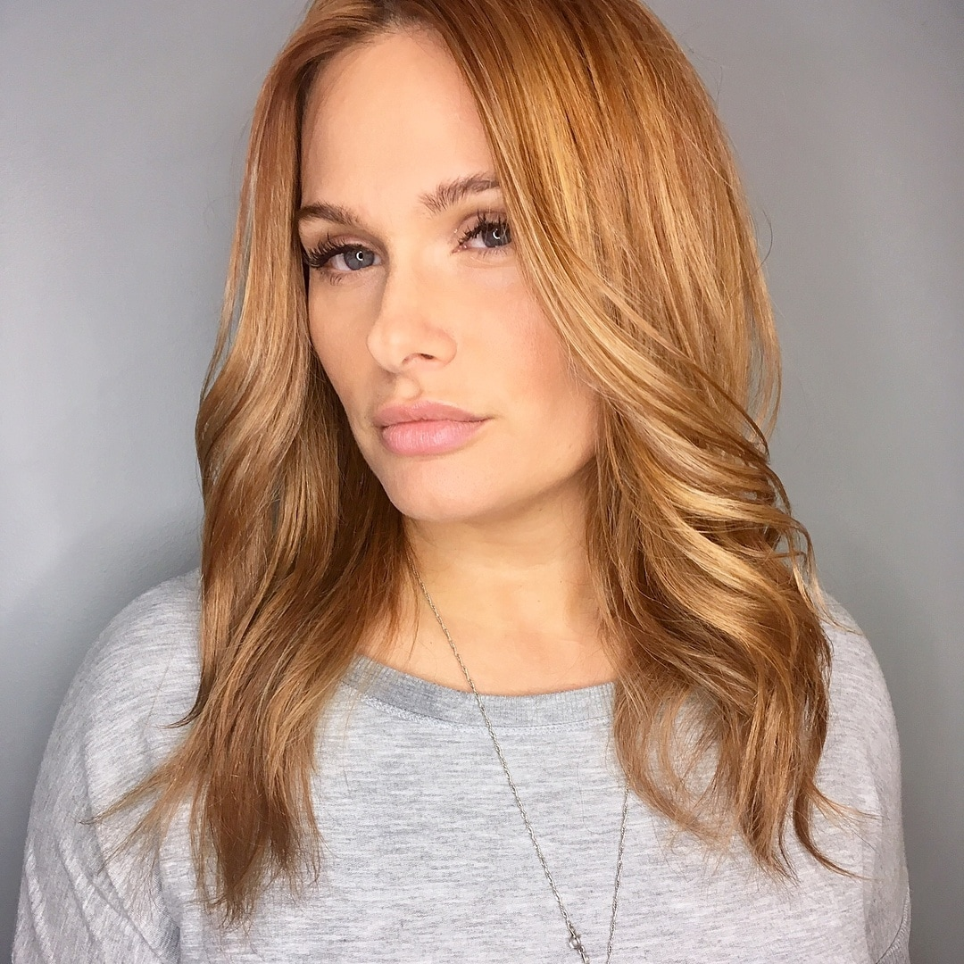 Woman with cinnamon blonde hair colour curled at the ends