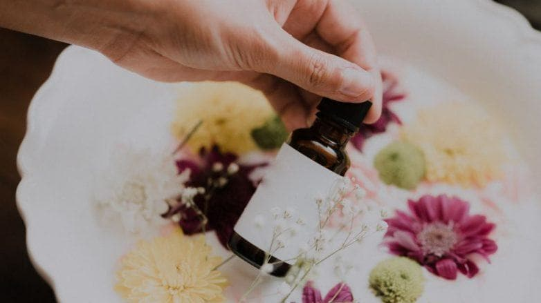 Hand holding a brown bottle in front of a bowl of flowers