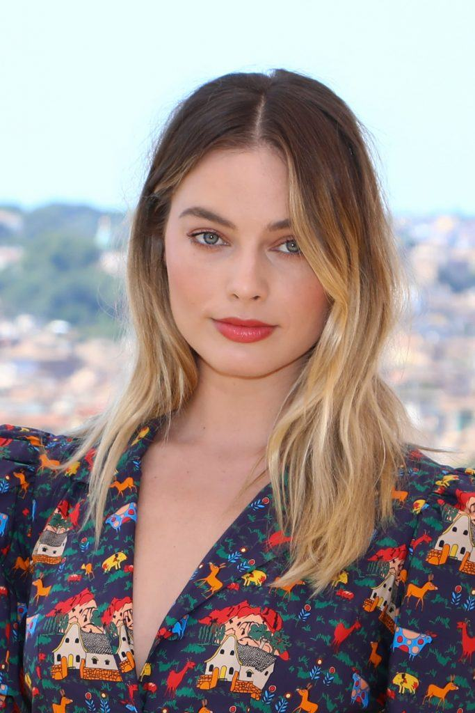 Margot Robbie with brunette to blonde hair with grown-out roots